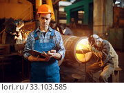 Master with notebook and welder on factory. Стоковое фото, фотограф Tryapitsyn Sergiy / Фотобанк Лори