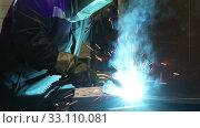 Купить «Welder in overalls and protective mask working in the shop  at the factory. Industrial theme», видеоролик № 33110081, снято 15 февраля 2020 г. (c) Алексей Кузнецов / Фотобанк Лори