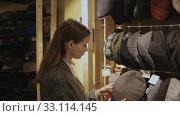 Купить «Young focused woman shopping hats in modern store», видеоролик № 33114145, снято 18 февраля 2020 г. (c) Яков Филимонов / Фотобанк Лори