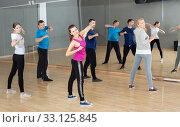 Купить «Females and males stretching at dance class», фото № 33125845, снято 7 июля 2020 г. (c) Яков Филимонов / Фотобанк Лори
