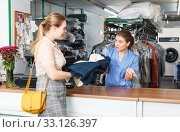 Купить «Worker checking clothes in dry cleaner», фото № 33126397, снято 9 мая 2018 г. (c) Яков Филимонов / Фотобанк Лори
