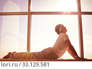 Купить «Silhouette of female doing physical exercise on background of window», фото № 33129581, снято 5 июля 2020 г. (c) PantherMedia / Фотобанк Лори