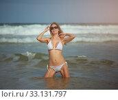 Купить «Young slim beautiful woman stay and posing in the sea or ocean waves», фото № 33131797, снято 21 июля 2019 г. (c) katalinks / Фотобанк Лори