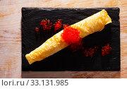 Купить «Roll of thin pancake with red caviar», фото № 33131985, снято 3 апреля 2020 г. (c) Яков Филимонов / Фотобанк Лори