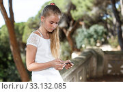 Купить «Teenage cute girl using smartphone at bridge at sunny day outdoor», фото № 33132085, снято 20 июля 2018 г. (c) Яков Филимонов / Фотобанк Лори