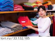 Купить «Young Chinese girl looking for fashionable mens shirt in clothing store», фото № 33132185, снято 28 марта 2020 г. (c) Яков Филимонов / Фотобанк Лори