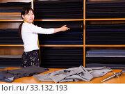Купить «Saleswoman offering cloth in textile shop», фото № 33132193, снято 25 февраля 2020 г. (c) Яков Филимонов / Фотобанк Лори