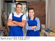 Portrait of smiling man and woman in work overalls in room during finishing work. Стоковое фото, фотограф Яков Филимонов / Фотобанк Лори