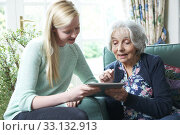 Granddaughter Showing Grandmother How To Use Digital Tablet. Стоковое фото, фотограф Ian Allenden / PantherMedia / Фотобанк Лори