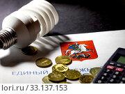 Купить «Лампочка рублевые монеты лежат на платежке за жилищно-коммунальные услуги города Москвы, Россия», фото № 33137153, снято 15 февраля 2020 г. (c) Николай Винокуров / Фотобанк Лори