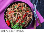 spicy slow-cooked pulled beef with chili pepper in a bow on a black wooden table, horizontal view from above, flatlay, close-up. Стоковое фото, фотограф Oksana Zh / Фотобанк Лори