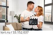 Купить «happy couple in white t-shirts with clapperboard», фото № 33152037, снято 6 октября 2019 г. (c) Syda Productions / Фотобанк Лори