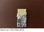 Купить «white chocolate bar in foil wrapper on brown», фото № 33152213, снято 1 февраля 2019 г. (c) Syda Productions / Фотобанк Лори