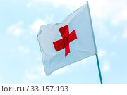 Russia, Samara, June 2019: flag with a red cross develops against a blue sky. Red Cross emblem of the international Red Cross, international humanitarian organizations. Редакционное фото, фотограф Акиньшин Владимир / Фотобанк Лори