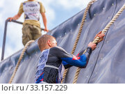 Купить «Russia, Samara, June 2019: a young sports man with the help of a rope overcomes the most difficult obstacles in the race of Everest heroes.», фото № 33157229, снято 8 июня 2019 г. (c) Акиньшин Владимир / Фотобанк Лори