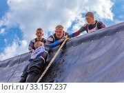 Купить «Russia, Samara, June 2019: a young sports man with the help of a rope overcomes the most difficult obstacles in the race of Everest heroes.», фото № 33157237, снято 8 июня 2019 г. (c) Акиньшин Владимир / Фотобанк Лори
