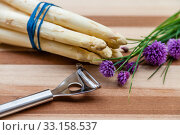 Asparagus and peeler on a wooden board. Стоковое фото, фотограф Sabine Katzenberger / PantherMedia / Фотобанк Лори