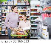 Купить «Young woman and girl with shopping cart», фото № 33160533, снято 5 января 2017 г. (c) Яков Филимонов / Фотобанк Лори