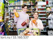 Купить «Woman customer with girl looking for refreshing beverages», фото № 33160537, снято 5 января 2017 г. (c) Яков Филимонов / Фотобанк Лори