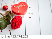 Купить «Single fresh red rose flower on the white wooden table with heart shaped sequins sprinkled around, candles and gift in box. Valentines or love concept. With copy space.», фото № 33174205, снято 2 апреля 2020 г. (c) easy Fotostock / Фотобанк Лори