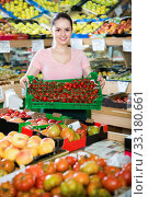 Купить «Friendly attractive saleswoman with crate with tomatoes in supermarket», фото № 33180661, снято 14 октября 2017 г. (c) Яков Филимонов / Фотобанк Лори