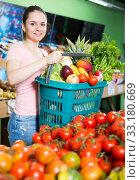 Купить «Satisfied woman with basket of fruits and vegetables in store», фото № 33180669, снято 14 октября 2017 г. (c) Яков Филимонов / Фотобанк Лори