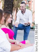 Купить «Young male is acquaintance with girls who are sitting on bench», фото № 33180685, снято 18 октября 2017 г. (c) Яков Филимонов / Фотобанк Лори