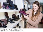 Купить «Cheerful woman is choosing ankle boots», фото № 33180813, снято 13 декабря 2017 г. (c) Яков Филимонов / Фотобанк Лори