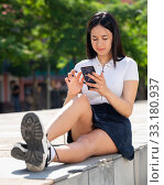 Купить «Young positive girl chatting on phone in the city center», фото № 33180937, снято 15 июня 2019 г. (c) Яков Филимонов / Фотобанк Лори
