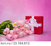 Bouquet of pink tulips and a red box with a gift on a pink background. Стоковое фото, фотограф Светлана Валуйская / Фотобанк Лори
