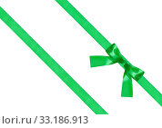 one green bow knot on two diagonal silk ribbons. Стоковое фото, фотограф Valery Vvoennyy / PantherMedia / Фотобанк Лори