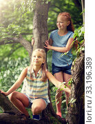 Купить «two happy girls climbing up tree in summer park», фото № 33196389, снято 24 июля 2016 г. (c) Syda Productions / Фотобанк Лори