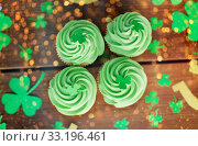 Купить «green cupcakes and shamrock on wooden table», фото № 33196461, снято 31 января 2018 г. (c) Syda Productions / Фотобанк Лори