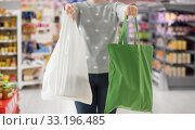 Купить «woman with tote for shopping and plastic bag», фото № 33196485, снято 3 мая 2019 г. (c) Syda Productions / Фотобанк Лори