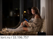 woman with tablet pc sitting on windowsill at home. Стоковое фото, фотограф Syda Productions / Фотобанк Лори