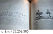 Купить «Ufa, Russia - FEB 15: man leafs through an old German physics textbook circa 1890 on February 14, 2015 in Ufa, Russia. Close up», видеоролик № 33202585, снято 14 февраля 2015 г. (c) Mikhail Erguine / Фотобанк Лори