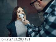 Maniac kidnapper taping his victim's mouth shut. Стоковое фото, фотограф Tryapitsyn Sergiy / Фотобанк Лори