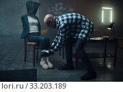Maniac kidnapper taping his female victim's legs. Стоковое фото, фотограф Tryapitsyn Sergiy / Фотобанк Лори