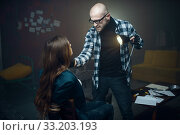 Купить «Maniac shines a flashlight in face of his victim», фото № 33203193, снято 13 ноября 2019 г. (c) Tryapitsyn Sergiy / Фотобанк Лори