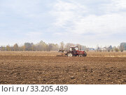 Red Tractor Plowing in Autumn. Стоковое фото, фотограф Franco Nadalin / PantherMedia / Фотобанк Лори