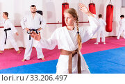 Купить «Tween girl mastering new taekwondo moves during group class with male coach», фото № 33206497, снято 9 июля 2020 г. (c) Яков Филимонов / Фотобанк Лори