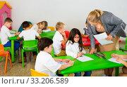 Female teacher helping schoolkids drawing with color pencils in classroom. Стоковое фото, фотограф Яков Филимонов / Фотобанк Лори