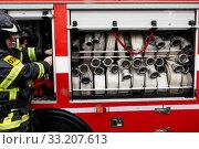 Сотрудник МЧС работает у пожарной машины в городе Москве, Россия (2020 год). Редакционное фото, фотограф Николай Винокуров / Фотобанк Лори