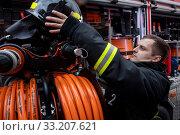 Купить «Сотрудник пожарного расчета у машины во время показательного смотра пожарной техники в честь 30 летия МЧС на ВДНХ в городе Москве, Россия», фото № 33207621, снято 23 февраля 2020 г. (c) Николай Винокуров / Фотобанк Лори
