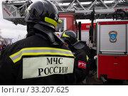 Купить «Сотрудники пожарного расчета стоит у пожарной машины во время показательного смотра пожарной техники в честь 30 летия МЧС на ВДНХ в городе Москве, Россия», фото № 33207625, снято 23 февраля 2020 г. (c) Николай Винокуров / Фотобанк Лори