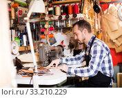 Male worker stitching new belt. Стоковое фото, фотограф Яков Филимонов / Фотобанк Лори