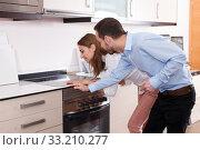 Купить «Couple choosing household appliances for kitchen», фото № 33210277, снято 11 апреля 2018 г. (c) Яков Филимонов / Фотобанк Лори
