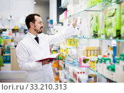 Pharmacist writing down assortment of drugs. Стоковое фото, фотограф Яков Филимонов / Фотобанк Лори