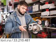 male engineer chooses circular saw in tool store. Стоковое фото, фотограф Яков Филимонов / Фотобанк Лори