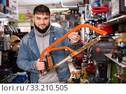 Portrait adult male with hacksaw in tools store. Стоковое фото, фотограф Яков Филимонов / Фотобанк Лори